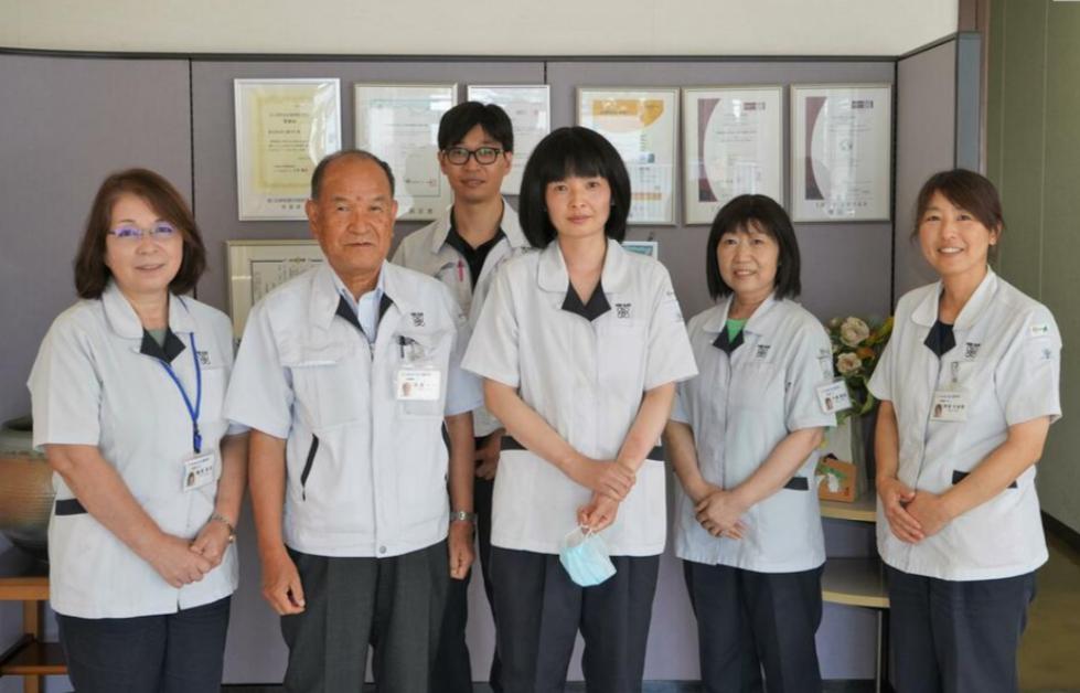 回国前,王惠(中间)和公司社长(左二)及员工合影(丹波新闻)